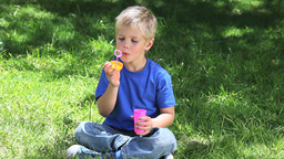 Boy playing with bubbles in a park Stock Video Footage