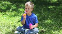 Boy playing with bubbles in a park Footage