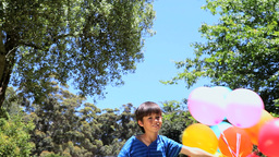 Boy playing with rubber balloon in a park Stock Video Footage