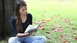 Woman reading a book in a park Stock Video Footage