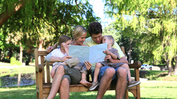 Family reading a book while sitting on a bench Footage