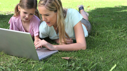 Woman and a girl looking at a laptop Footage