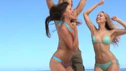 Women and man jumping on the beach Stock Video Footage