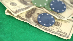 Poker coins and bills thrown on a gambling table Live Action