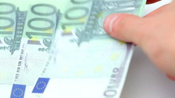 Hundred euro bills placed by a hand on a table Stock Video Footage