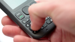 Hand dialing a number on a mobile telephone Live Action