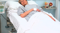 Female patient lying on a bed while closing her ey Footage