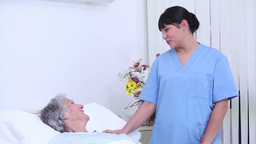 Nurse talking to a senior woman in her bed Footage