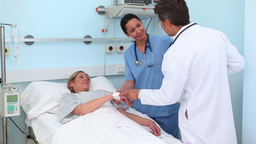 Doctor and nurse looking at a blonde patient Stock Video Footage