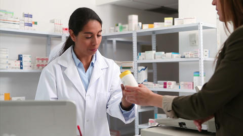 Smiling female pharmacist handing drugs to a custo Footage