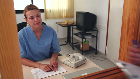Nurse looking at files at a reception desk Stock Video Footage