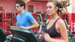 Woman and man running on a treadmill Footage