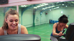 Women cycling on exercise bikes and chatting Footage