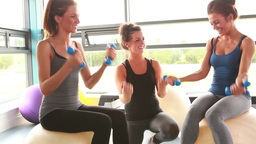 Trainer helping women on exercise balls lifting weights Footage