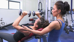 Trainer helping woman lifting weights Stock Video Footage