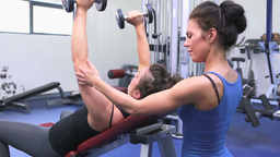 Trainer helping woman lifting weights Footage