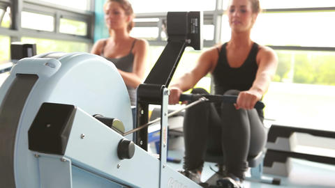 Two women drawing on row machine Stock Video Footage