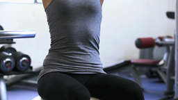 Woman sitting on exercise ball and lifting weights Footage