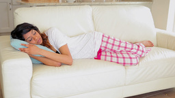 Woman lying on the couch sleeping Stock Video Footage