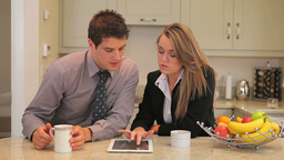 Couple sitting in the kitchen with tablet pc Footage