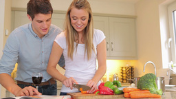 Woman cutting vegetables with man reading cookbook Footage