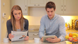 Woman reading newspaper with man holding a tablet PC Stock Video Footage