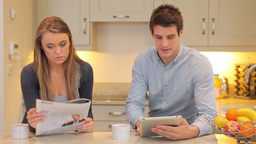Woman reading newspaper with man holding a tablet Stock Video Footage
