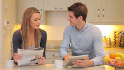 Woman reading newspaper with man holding a tablet  Footage