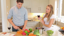 Man is cutting vegetables with woman drinking wine Stock Video Footage