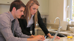 Couple sitting in the kitchen looking at laptop Stock Video Footage