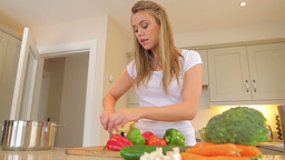 Woman cutting vegetables putting in a pot with man Footage