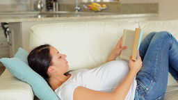 Pregnant woman reading a book on the sofa Footage