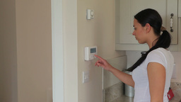Woman turning on home alarm system Footage