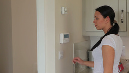 Woman turning on home alarm system Stock Video Footage