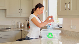Woman putting bottles into recycling bin Footage