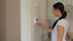 Woman turning on alarm system Footage
