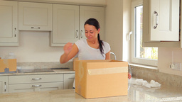 Woman packing moving box with man carrying boxes Footage