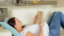 Pregnant woman relaxing and reading Footage
