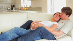 Expecting couple relaxing on sofa Footage