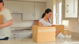 Woman packing up boxes and man moving them Footage