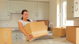 Woman bringing moving boxes into kitchen Footage