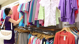Woman looking through clothes Stock Video Footage