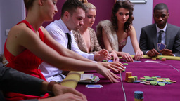 People at poker table placing bets woman in red dr Footage