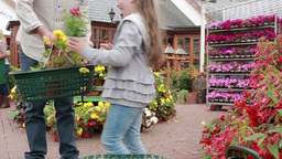 Little girl choosing plant and putting it in basket Stock Video Footage