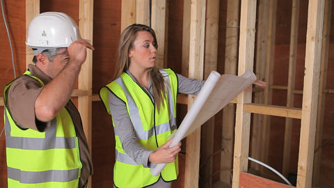 Architect discussing plan with builder Footage