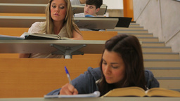 Students working and writing in lecture hall Footage