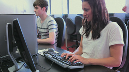 Student working on computer while her teacher come Stock Video Footage