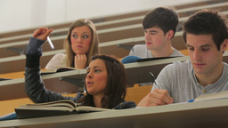 Woman sitting at the lecture hall with hand up Footage