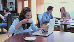 Smiling woman drinking coffee and using laptop Stock Video Footage
