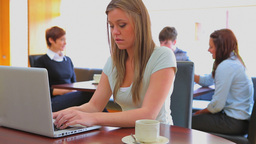 Smiling woman typing on notebook in canteen Stock Video Footage